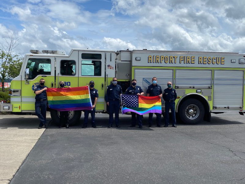 Lani Hill and other Portland Airport Firefighters stand in front of fire truck with Pride flags